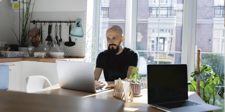 Man sitting at kitchen table working on his laptop