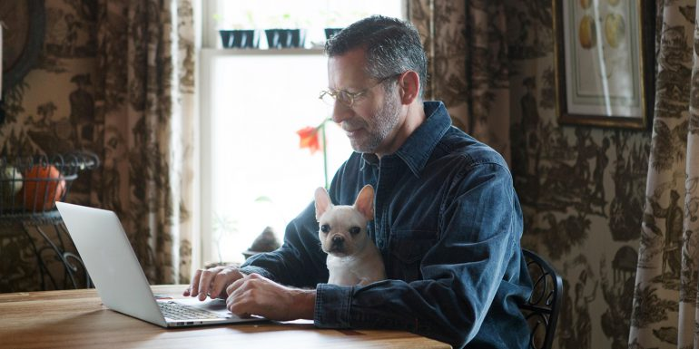 Man working at kitchen table on laptop with his dog