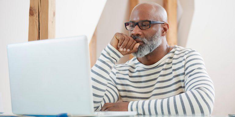 Older man at home working on laptop