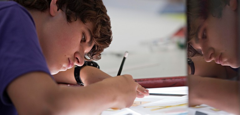 student drawing on light table