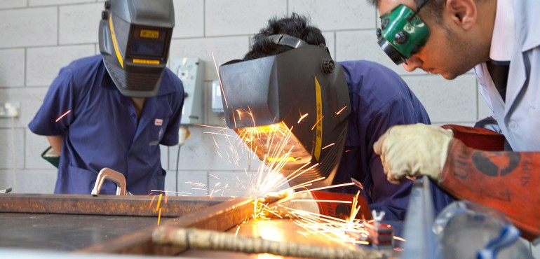 students welding a metal frame