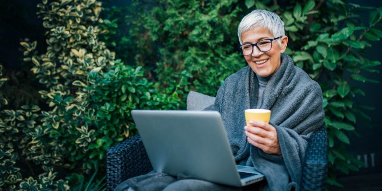 Woman sitting outside on her laptop with cup of tea