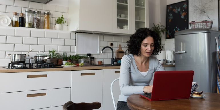Woman working on laptop at kitchen table