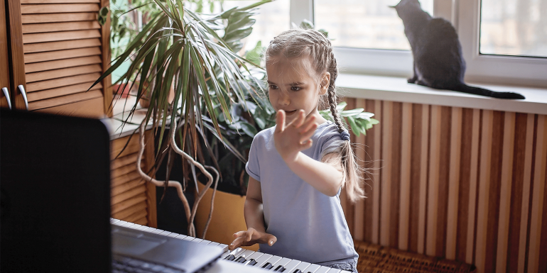 Young girl taking virtual music lesson