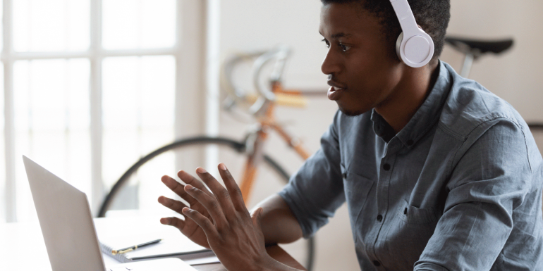 young man with headphones talking on his laptop