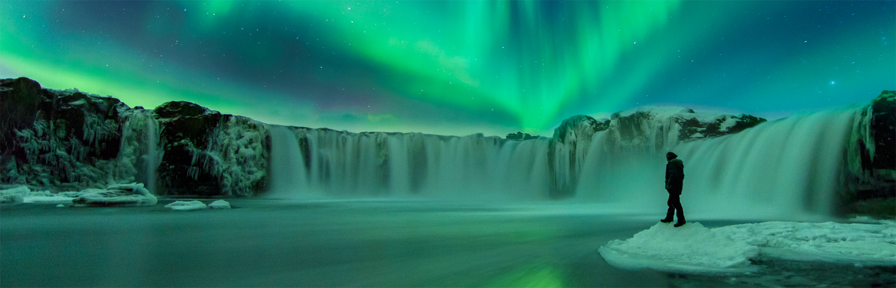 Person on ice looking out at a waterfall under the Northern Lights