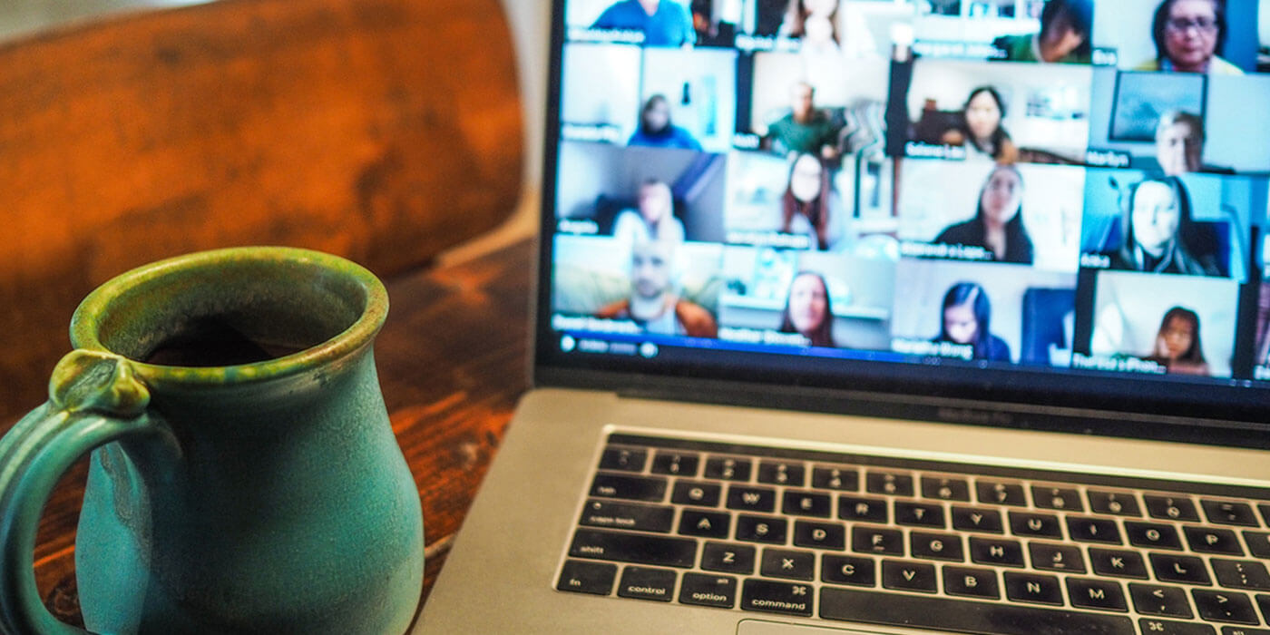 Mug sitting beside laptop showing video conference call