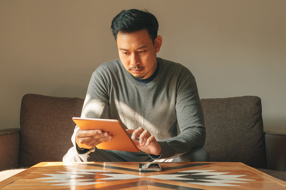 image of male adjunct sitting in chair, reviewing content on a electronic tablet